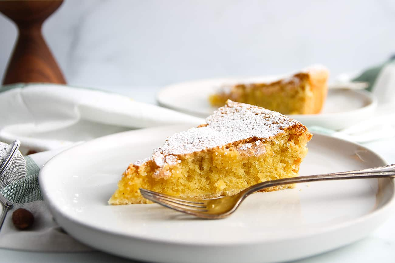 Slice of Galician Almond Tart dusted with powdered sugar