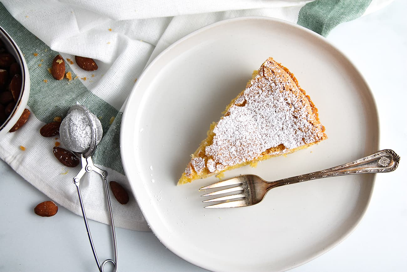 Slice of Tarta de Santiago dusted with powdered sugar