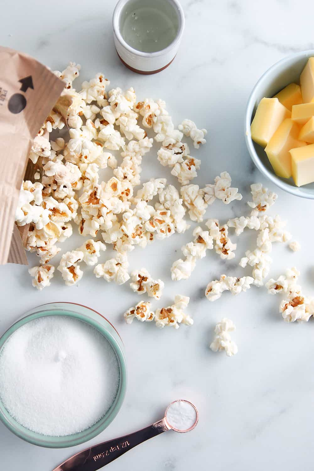 Ingredients for microwave caramel corn on a marble surface