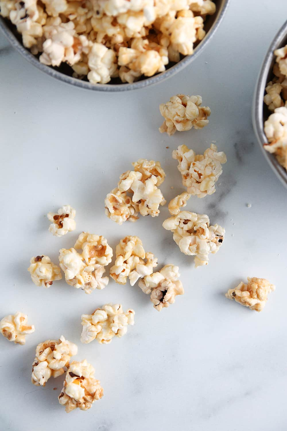 Pieces of microwave caramel corn scattered on a marble surface