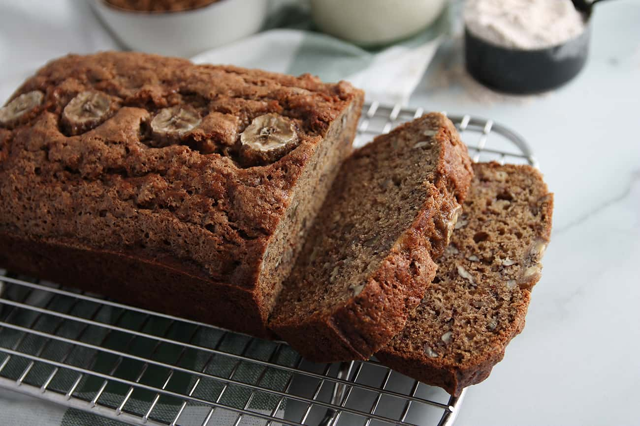 Angled view of sliced loaf of sourdough banana bread on a cooling rack with a measuring cup of flour in the backgroun