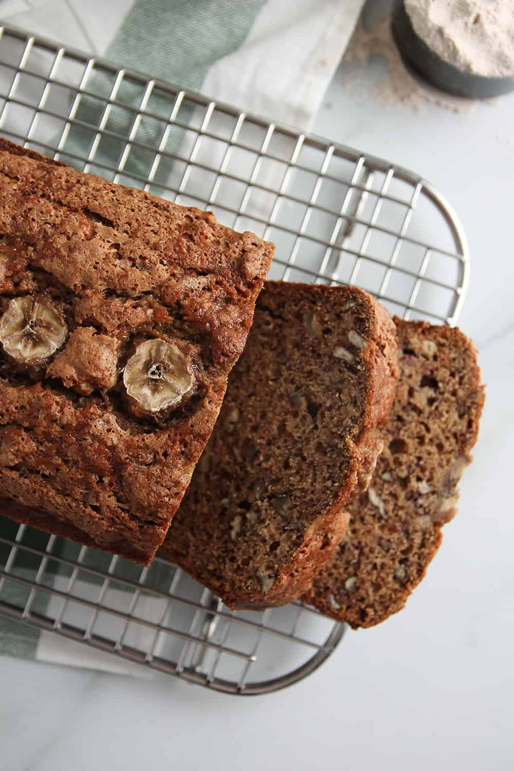 Overhead view of sliced loaf of vegan sourdough banana bread on a cooling rack, set on a marble countertop