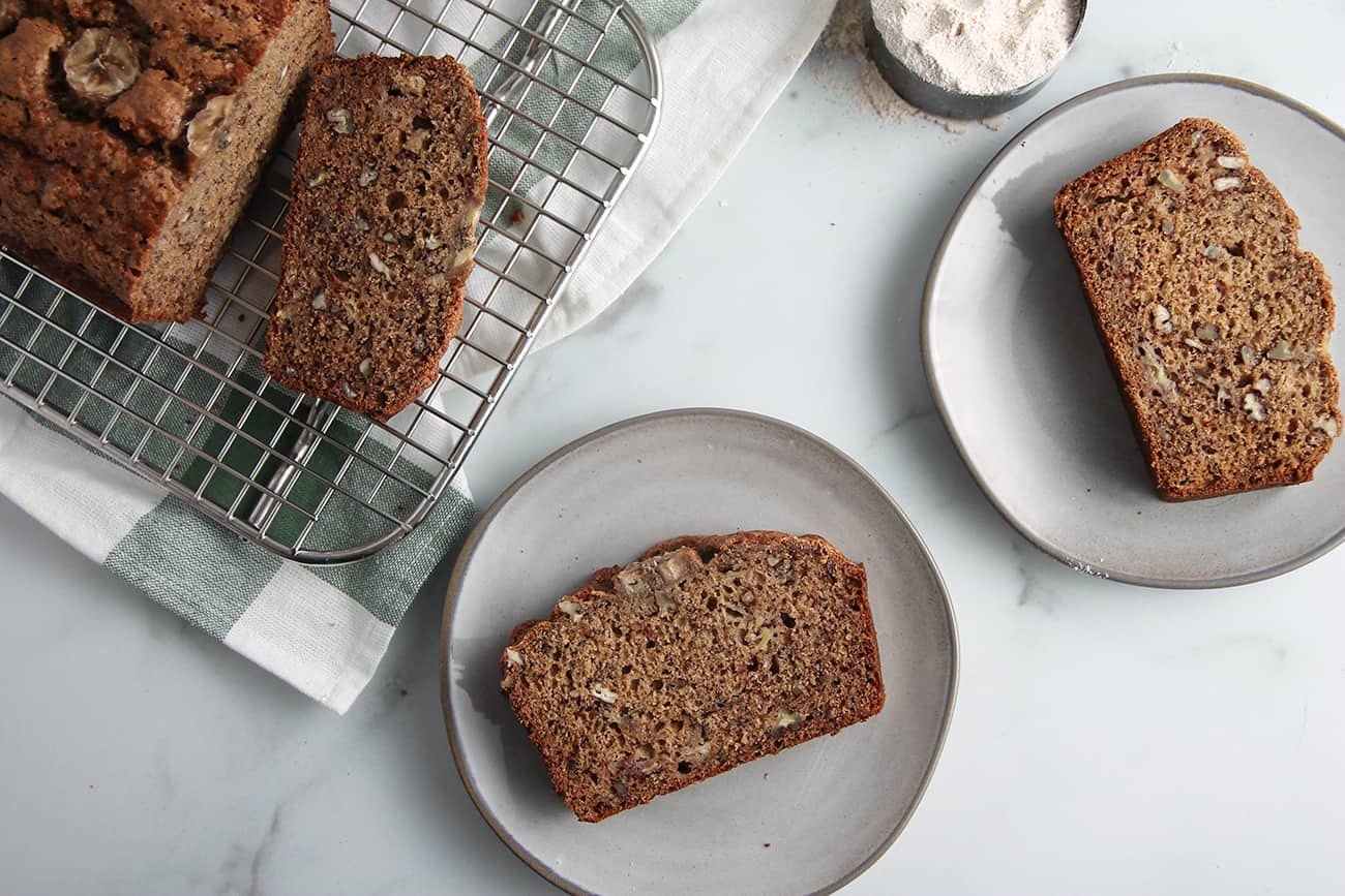 Overhead view of 2 gray plates with slices of sourdough banana bread next to a sliced loaf of banana bread on a cooling rack