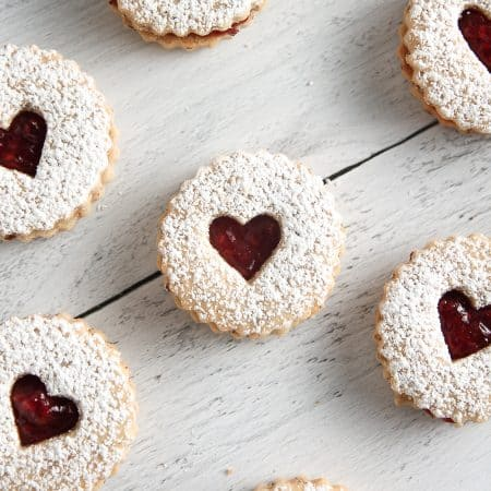Raspberry Linzer Cookies sandwich bright and tangy raspberry jam between two almond cookies. They're as delicious as they are beautiful!