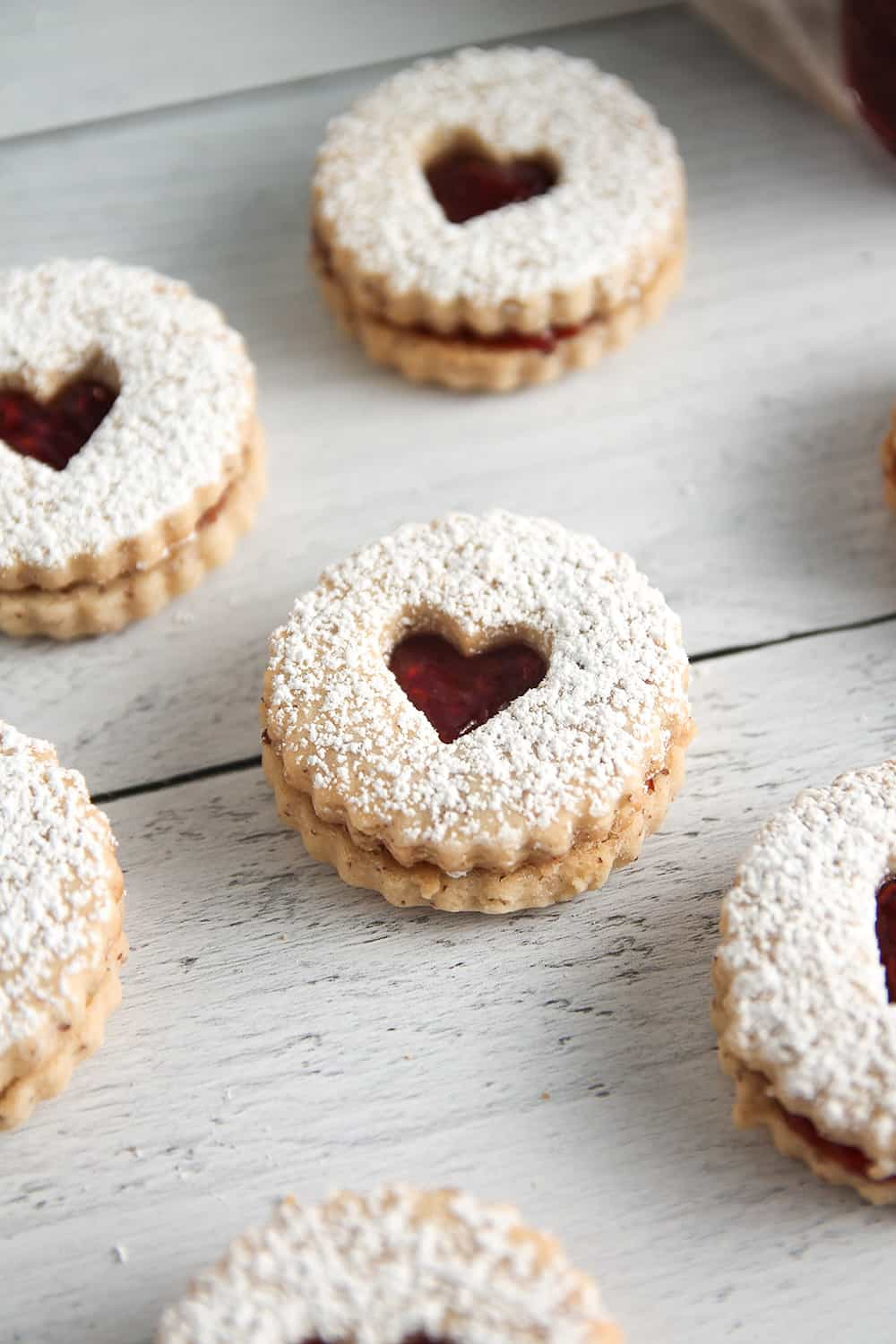 Raspberry jam gets sandwiched between two almond cookies to make traditional Raspberry Linzer Cookies.