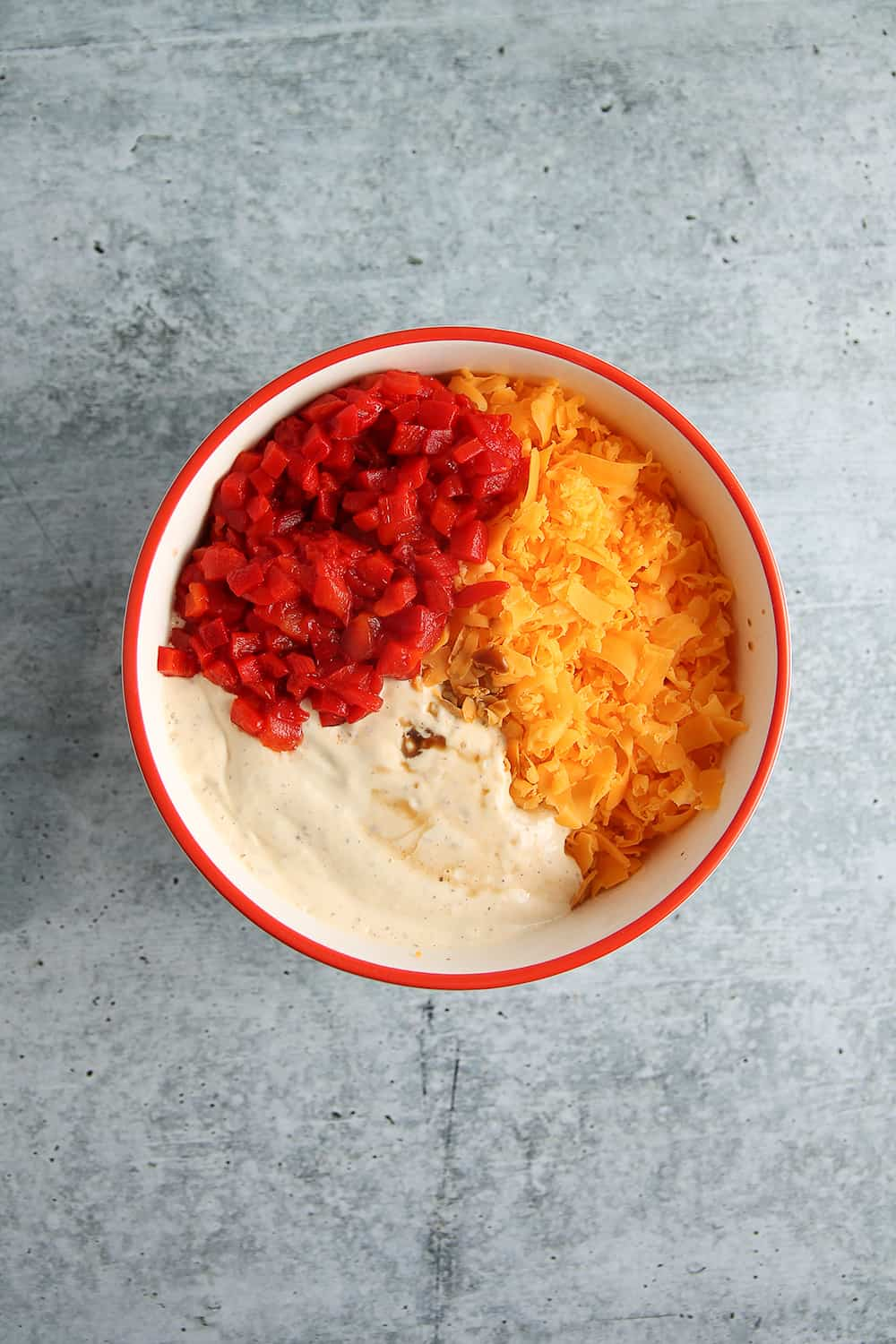 Overhead view of bowl with diced pimentos, shredded cheddar cheese and mayonnaise