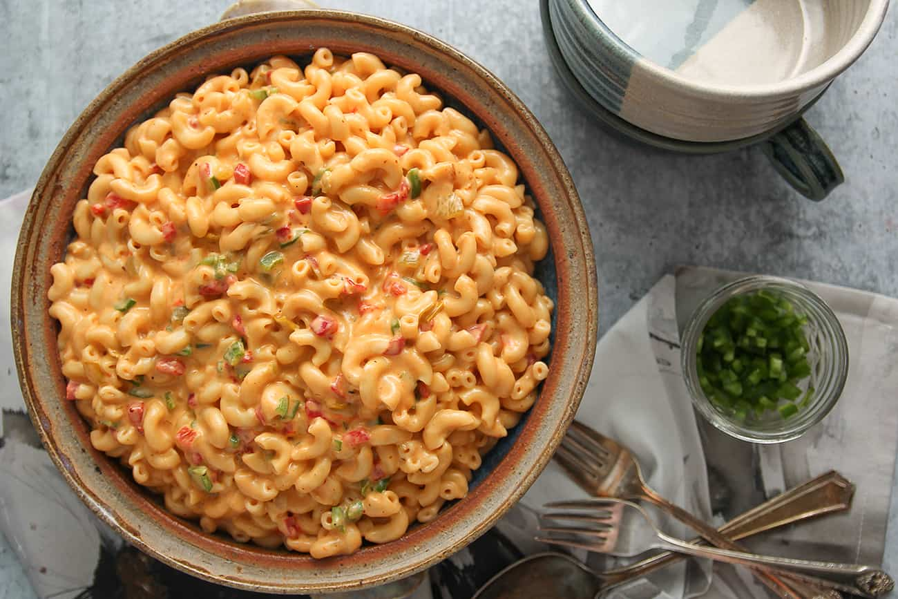 Large bowl of green chili macaroni and pimento cheese alongside serving bowls and diced jalapenos