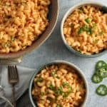 Large bowl of macaroni and pimento cheese alongside two serving bowls, forks and sliced jalapenos