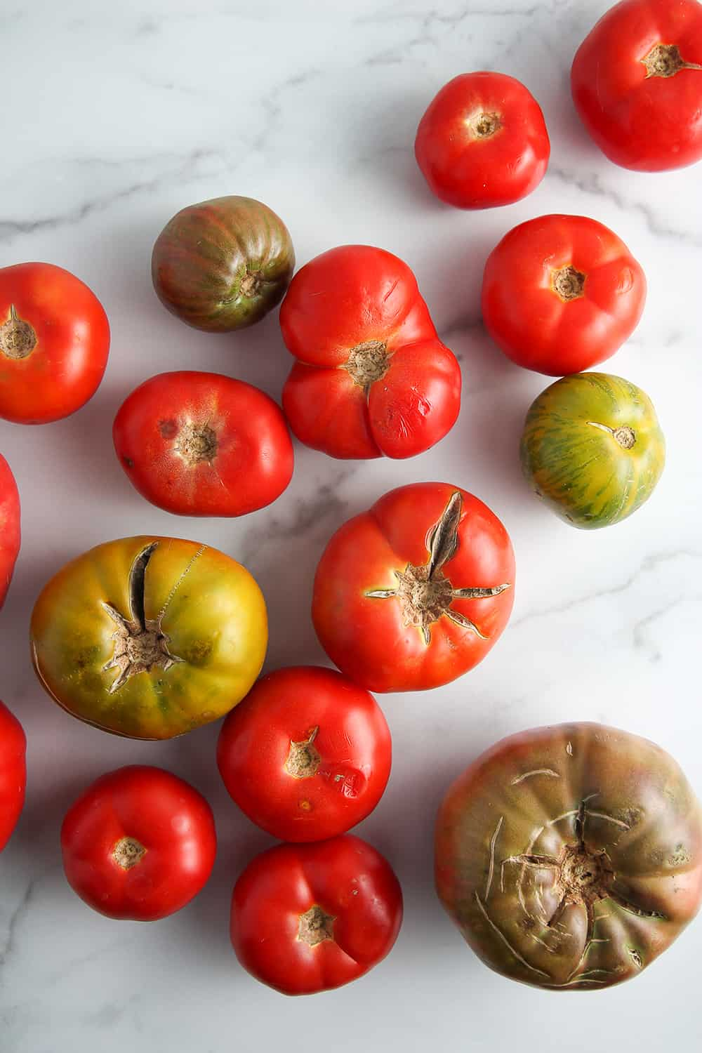 Assorted fresh heirloom tomatoes on a marble surface