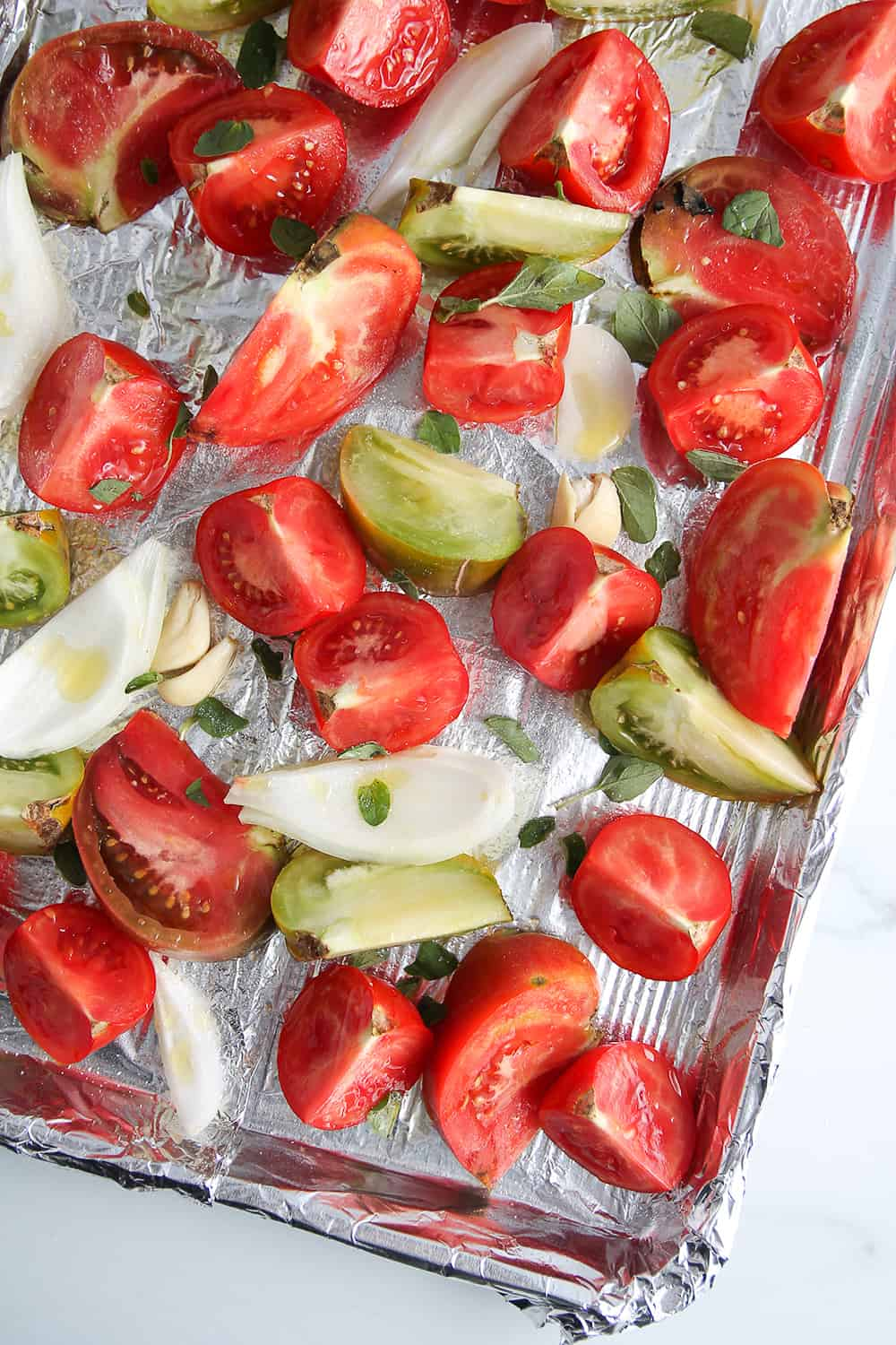 Fresh tomatoes and onions on a foil-lined sheet pan, ready to roast