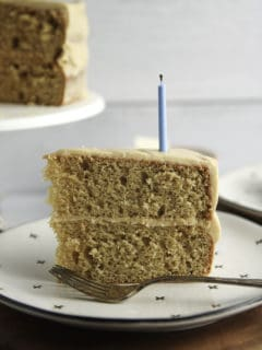 Slice of peanut butter layer cake with a birthday candle in it