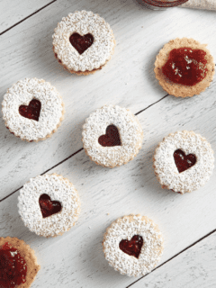 Raspberry Linzer Cookie sandwiches on a white surface